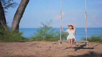 Young asian woman sit on swing around beach sea