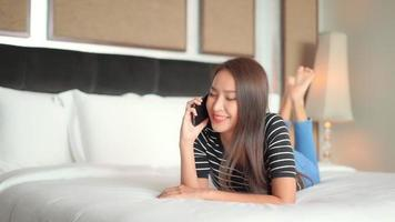 Woman use mobile phone on bed for talking