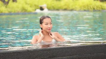 Young asian woman relaxes leisure around swimming pool video