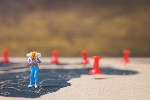 Miniature backpacker walking on a world map, tourism and travel concept photo