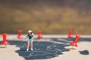 Miniature backpacker walking on a world map, tourism and travel concept