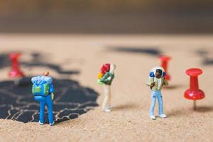 Miniature backpackers walking on a world map, tourism and travel concept