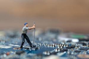 Persona en miniatura que trabaja en una placa de CPU, concepto de tecnología