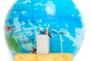 Miniature businessman speaking on a podium about Earth Day photo