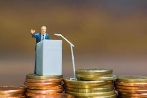 Miniature businessman speaking on a podium on a stack of coins, business and financial investment concept