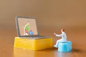 Miniature male patient consulting with a doctor using a video call on a laptop, online doctor concept