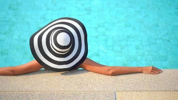 Asian woman wears straw hat around pool video