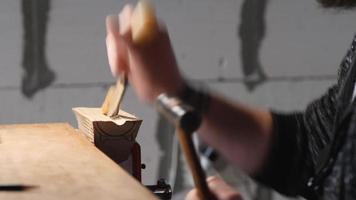 entalhador de madeira esculpe um suporte de madeira com um formão
