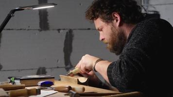 bearded man carves wooden product with chisel