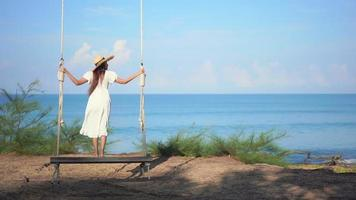 Woman Stands on Swing Around the Ocean Beach video