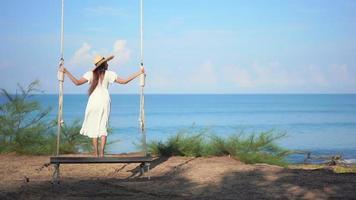 mulher em pé balançando ao redor da praia do oceano