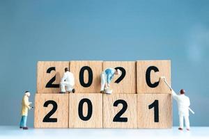 Trabajadores en miniatura que se unen para pintar el número 2021 y eliminar el número 2020, concepto de feliz año nuevo foto