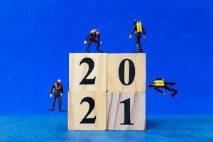 Buceadores en miniatura buceando alrededor de bloques de madera con el número 2021, concepto feliz año nuevo foto