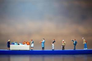 Personas en miniatura manteniendo la distancia en un centro comercial y un área pública, concepto de distanciamiento social foto