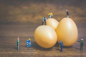 Miniature people working on Easter-eggs for Easter photo