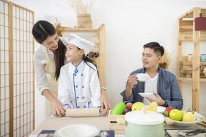 Happy family cooking biscuits together in kitchen photo