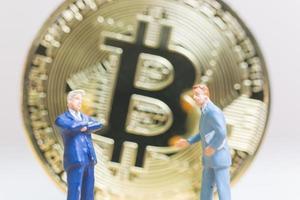 Empresarios en miniatura de pie delante de una moneda de criptomoneda bitcoin, concepto de negocio