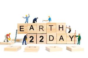 Miniature workers teaming up to build the word Earth Day 22 on wooden blocks, Earth day concept photo
