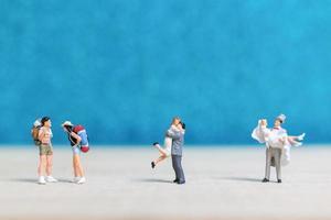 Gente en miniatura sobre un fondo azul. foto