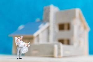 La novia y el novio en miniatura sobre un fondo azul. foto