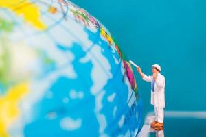 Miniature painter painting on a globe, Earth Day concept photo