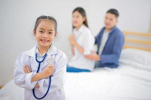 Girl dressed like a doctor at home photo
