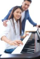 Couple playing piano together photo