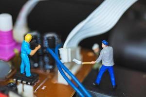 Trabajadores en miniatura que se unen para reparar circuitos electrónicos, concepto de trabajadores de la construcción