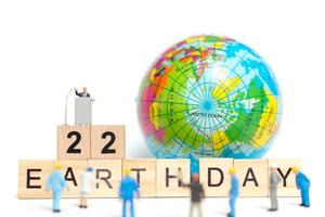 Miniature painters painting on a globe with wooden blocks showing Earth Day 22 on a white background, Earth Day concept photo