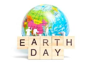 Miniature painters painting on a globe with wooden blocks showing Earth Day on a white background, Earth Day concept photo