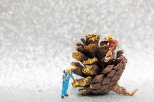 Miniature workers teaming up to prepare a Christmas pine cone, Christmas and Happy New Year concept