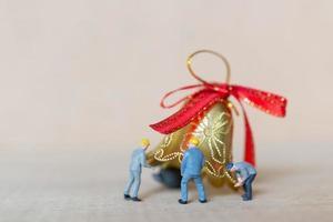 Trabajadores en miniatura que se unen para trabajar en un concepto de decoración navideña, navidad y feliz año nuevo foto