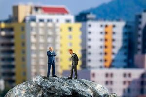 Miniature businessmen standing on a rock with buildings in the background photo