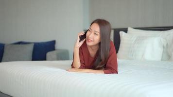 junge asiatische Frau spricht auf dem Handy auf dem Bett