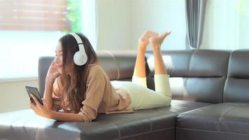 Woman Listens to Music on Sofa in Living Room video