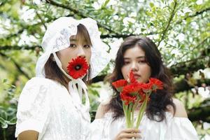 mujeres y flores rojas foto