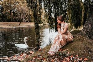 Woman wearing a dress looking at a swan