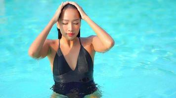 Young Asian Woman Relaxes Around Swimming Pool video