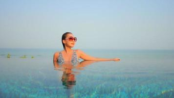 Asian Woman Relaxes Around Infinity Swimming Pool with Sea View video