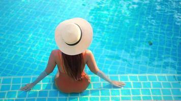 Joven mujer asiática usar sombrero de paja alrededor de la piscina