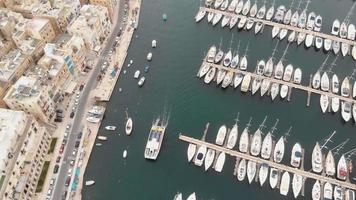 a volo d'uccello, panoramica riprese aeree 4K drone, di un porto turistico lungo un canale d'acqua tra due città mediterranee di Malta. video