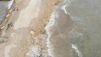 foto aérea de cima para baixo de pequenas ondas batendo na areia em marsaxlokk malta video