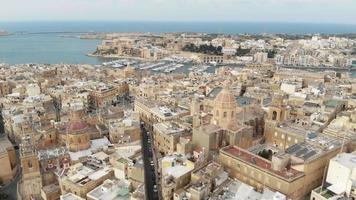 um retrocesso revela imagens de drones aéreos de 4k da paisagem urbana das 'três cidades de malta' ao longo da costa do oceano mediterrâneo. video