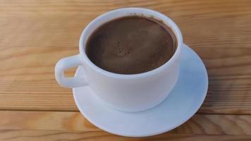 cinemografia de uma xícara de café branco com café em uma mesa de madeira