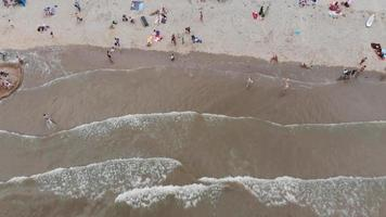 Revealing aerial footage of a crowded beach along a North Sea city shore of Zandoort, Netherlands.