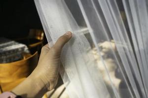 Woman's hand on the curtain