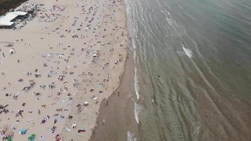 Aerial footage tilt revealing a coastline beach of the city of Zandoort, Netherlands along the North Sea.