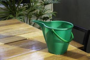 Green watering can on wooden table