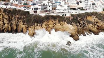 imagens aéreas de drones 4k recuando para revelar as ondas do mar batendo nas falésias da cidade balneária de albufeira, portugal. video