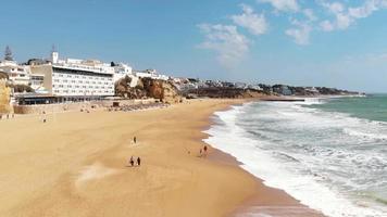 pessoas passeando ao longo da intocada praia de areia de albuferia, algarve. frente aérea